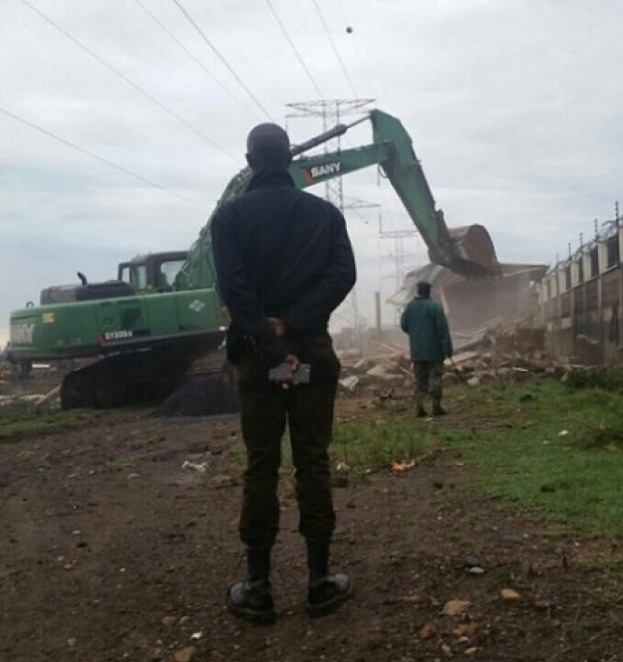 A man stands watch as an excavator pulls down illegal structures encroaching on power wayleave.