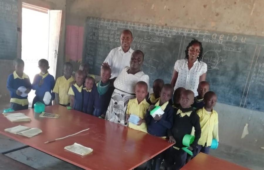 Corporate Communications Officers Erik Kathenya and Mary Gatheca with pupils of Kiamukuyu Primary with 2 of the 12 tables donated by Kenya Power as part of WezeshaJamii programme.