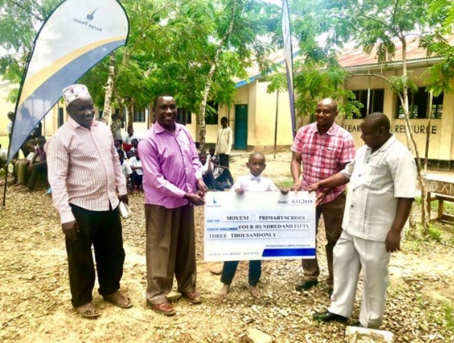 Ramadan Said a Std1 pupil at Moyeni Pry accompanied by CBM, Kwale County George Mwabusa holds a cheque of Shs. 450,000 which will aid in buying 100 desks for the school.