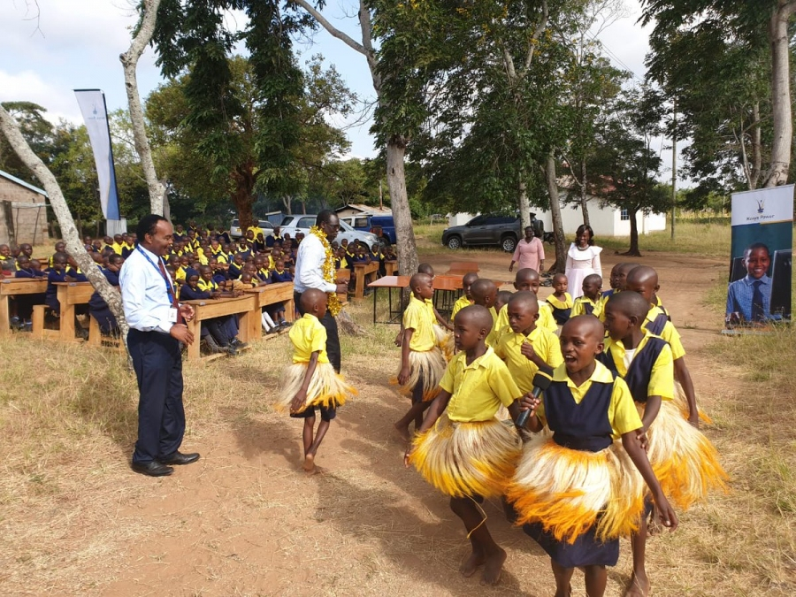 Ag. MD & CEO Jared Othieno joins jubilant pupils of Kiamukuyu Pry in song and dance during hand over of 12 tables and 60 desks donated under Wezesha Jamii programme.
