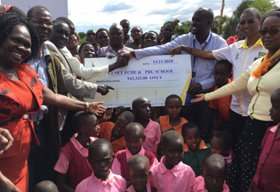 County Business Manager - Baringo County, Stephen Mwenesi, presents a dummy Cheque of Shs.943,325/- to Headteacher Donald Tanui, of Kenet ECDE & Pri Sch, in Mogotio, Baringo County.