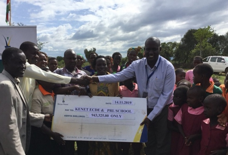 County Business Manager - Baringo County, Stephen Mwenesi, presents a dummy Cheque of Shs.943,325/- to Headteacher Donald Tanui, of Kenet ECDE & Pri Sch, in Mogotio, Baringo County