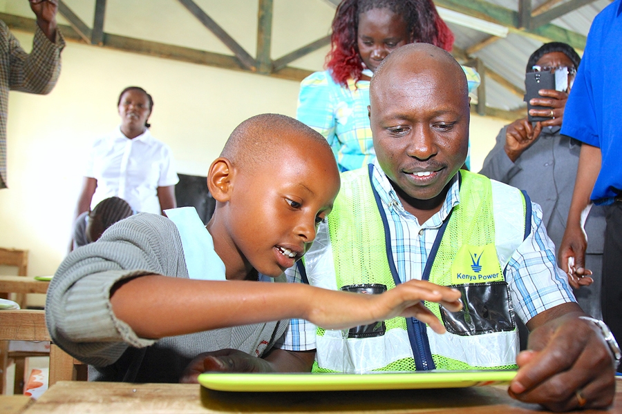 Stella Musyimi, a pupil at Katulu Pri. Sch. shows Ag. MD Dr. Ken Tarus how she uses her digital tablet.