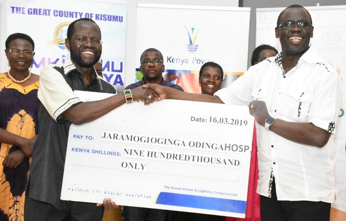 Ag. MD & CEO Eng. Jared Othieno handing over a cheque of KShs 900,000 to the Governor of Kisumu County Hon. Anyang Nyongo for the purchase of a cardiotochograph for JOOTRH.