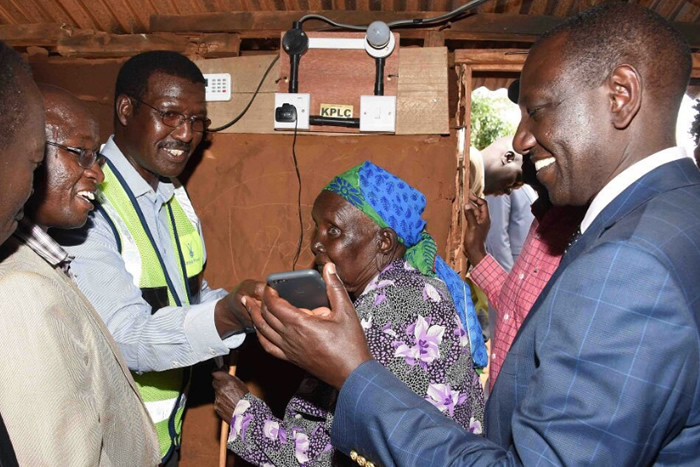 Kenya Power MD & CEO, Dr. Chumo assists Deputy President Hon. William Ruto to connect a phone charger in Nyamira.