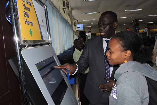 Ag. MD & CEO Eng. Jared Othieno assisting a customer with the self service kiosk the launch of our refurbished Electricity House Customer Service Centre - 24.09.2018