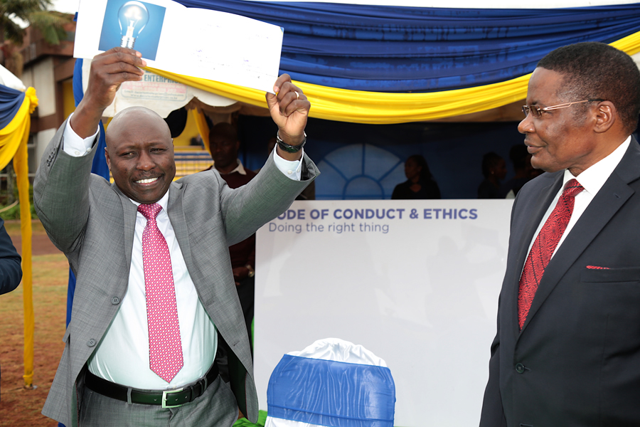 MD Dr. Ken Tarus displays the revised Code of Ethics policy to staff as board Chair Hon. Kenneth Marende looks on.